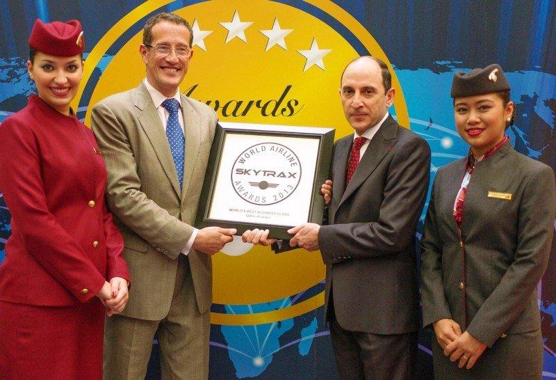 El CEO de Qatar Airways, Akbar Al Baker (Izq.), recibe el premio de Skytrax 2013 a la Mejor Business Class del Mundo; entregado por Richard Quest, de la CNN; flanqueados por miembros de la tripulación de cabina de la compañía.
