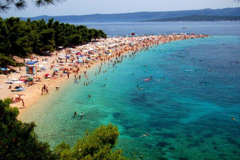 Una playa con turistas en la isla de Brac, Croacia. #shu#