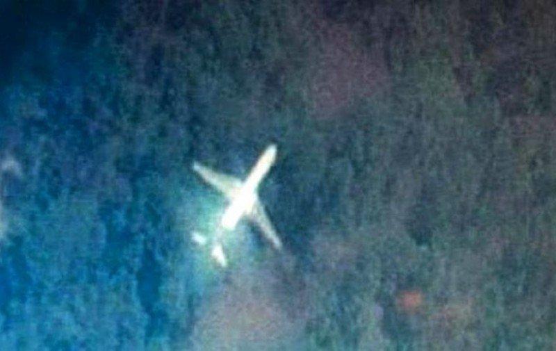 Imagen publicada en el portal Tomnod donde un avión con las características de un 777 sobrevuela a baja altura una zona de jungla sobre Malasia.