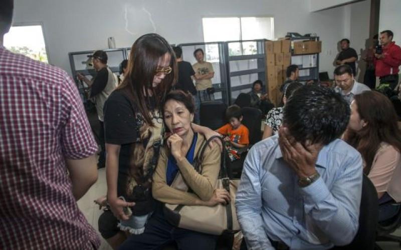 Familiares de los pasajeros del QZ8501 esperan noticias en el aeropuerto de Surabaya. / JUNI KRISWANTO (AFP)