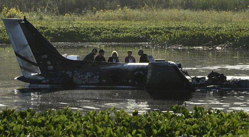 La jueza de Maldonado y rescatistas en los restos del avión en la Laguna del Sauce. Foto: AFP