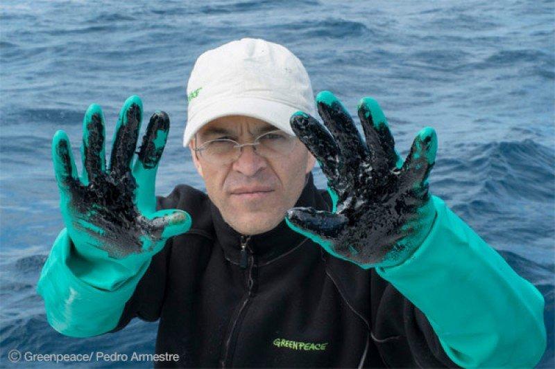 Un miembro de Greenpeace muestra restos de fuel del buque ruso hundido cerca de Canarias.