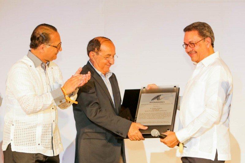 Los representantes de Asonahores entregan una placa de reconocimiento a Pablo Piñero.