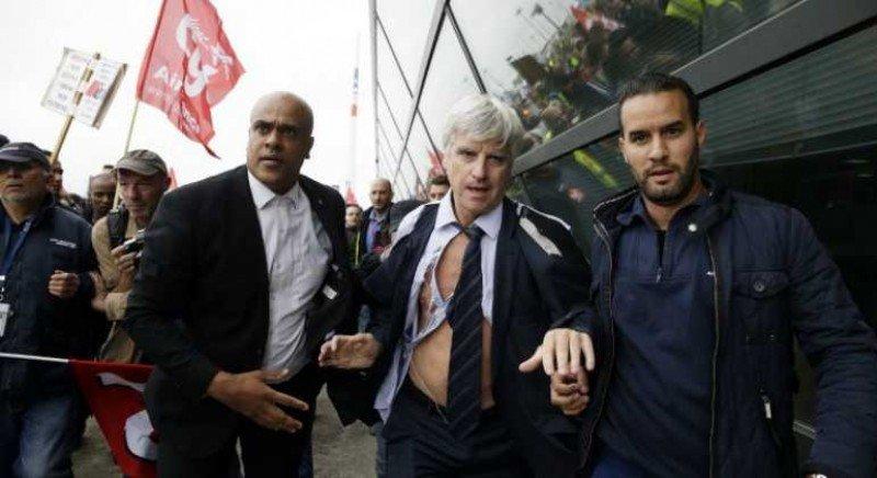 Pierre Plissonnier, director de vuelos de largo radio de Air France, ayudado por l apolicía y personal de seguridad para escaparse de los manifestantes que irrumpieron en una reunión entre la empresa y los sindicatos (Foto: AFP).