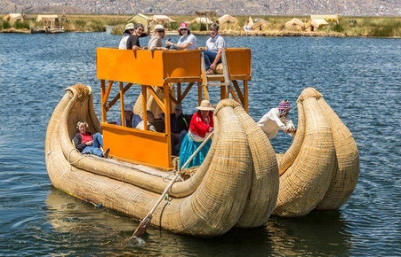 Turistas pasean por el lago Titicaca en una típica embarcación. #shu#
