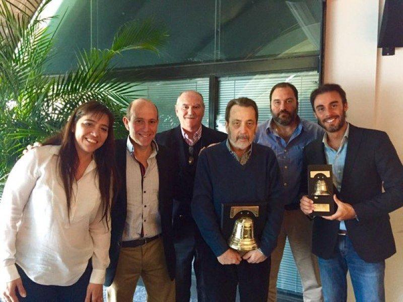 Directivos de Alas Uruguay con el premio Campana de Oro.