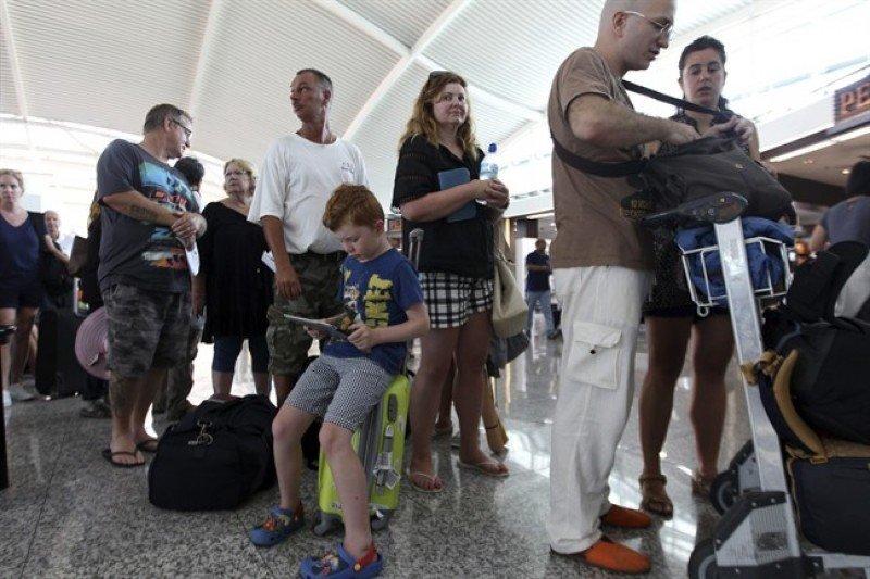 Pasajeros hacen cola ante los mostradores de las aerolíneas en el Aeropuerto Internacional de Ngurah Rai, en Bali, Indonesia, para concultar el estado de sus vuelos (Foto: AP Photo/Firdia Lisnawati).