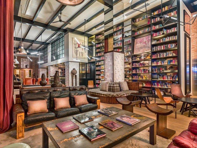 El lobby, presidido por una biblioteca con techos a doble altura y paredes de obra vista, tiene una marcada inspiración industrial.