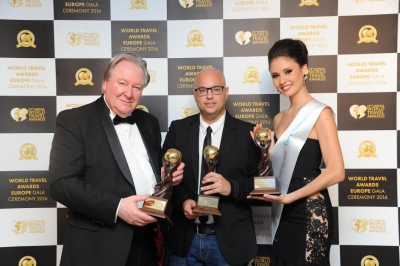De izq. a dcha, Graham Cooke, presidente y fundador de los World Travel Awards; Enrique Montes, director del Lopesan Baobab Resort, y una de las azafatas de la gala, sujetando los premios de Lopesan.