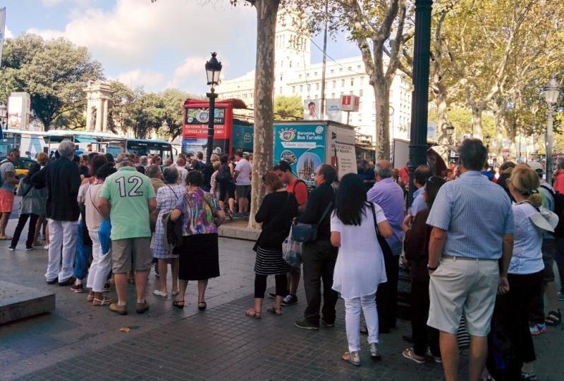 Turistas haciendo cola en la plaza Cataluña de Barcelona para subir al Bus Turístico