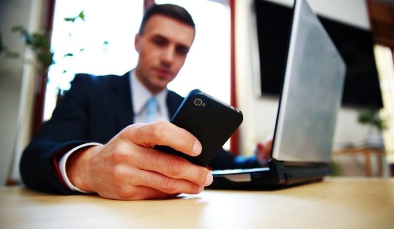Un viajero de negocios con su smartphone y ordenador portátil, dispositivos que suelen conectarse a la red wifi de un hotel.