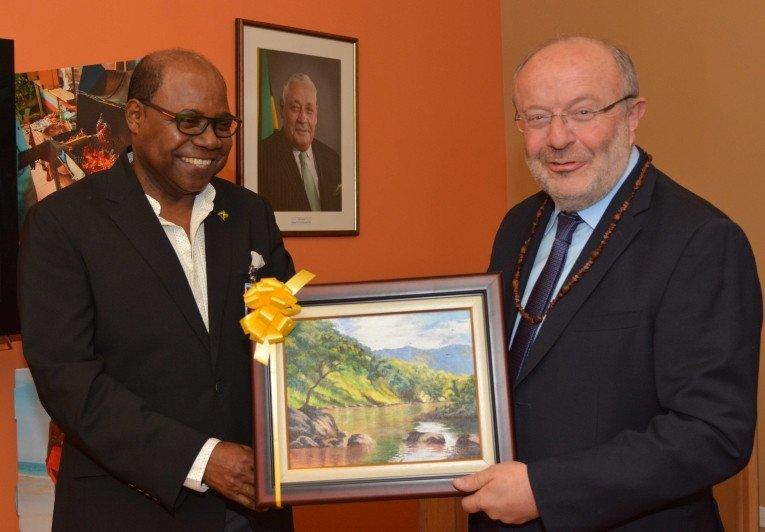 El ministro de Turismo, Hon Edmund Bartlett (izquierda) con el Secretario de Estado Español para la Cooperación Internacional para América Latina y el Caribe, Fernando García Casas, con un cuadro de regalo de bienvenida.