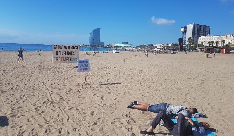 Dos personas duermen el sábado por la mañana en la playa de la Barceloneta, junto a unas pancartas de protesta colocadas por los vecinos.