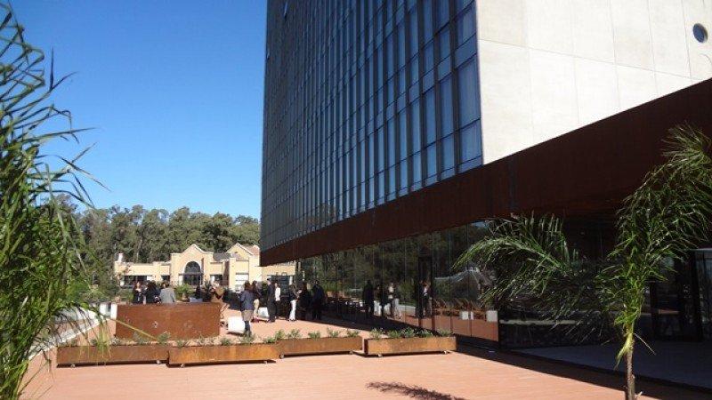 El estudio de arquitectura describe al hotel como 'un prisma ligero, una pantalla de vidrio, sobre un basamento más opaco, de acero corten, que sobre el acceso se hace un atrio techado de 24 metros que permite acceder mirando al lago, para luego ingresar'.