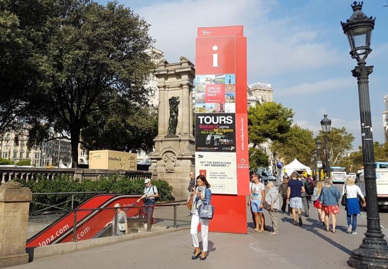 Un cartel en la plaza Cataluña de Barcelona anuncia excursiones a destinos cercanos como Montserrat o el Museo Dalí en Figueres.