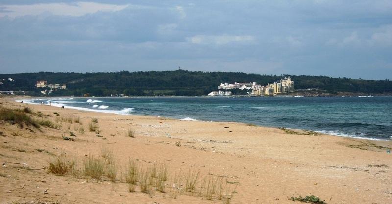 Una playa en Dyuni, Bulgaria, con un hotel al fondo.