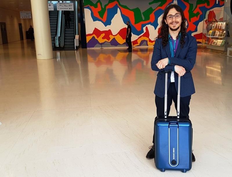 Maximillian Kovtun, presidente de TravelMate Robotics, junto a la maleta robot desarrollada por dicha empresa.