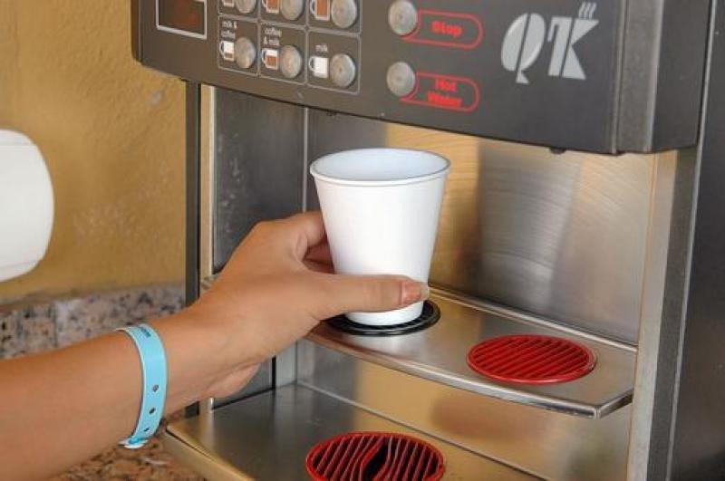 Un cliente se sirve un café en un vaso de plástico.