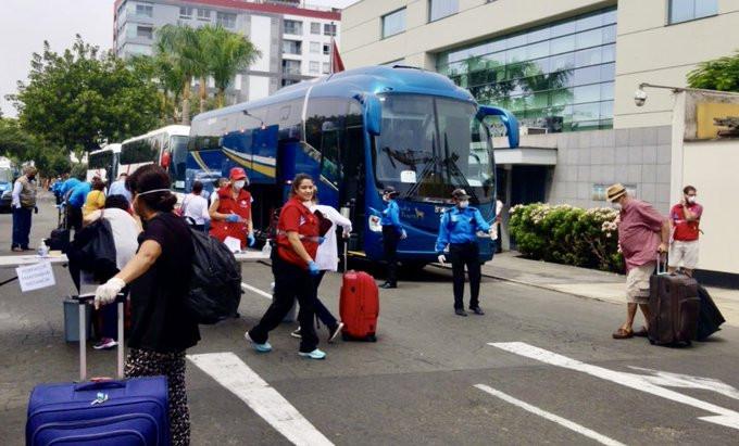 Canadienses embarcan buses en la embajada de Lima rumbo al aeropuerto. Foto: