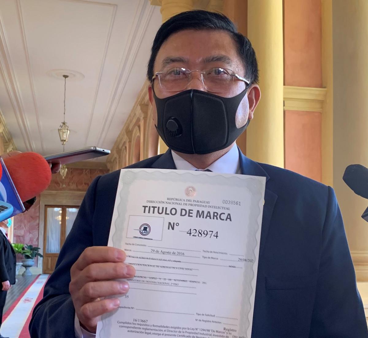 El titular de la DINA muestra el Titulo de Marca de LAP, propiedad del Estado paraguayo.